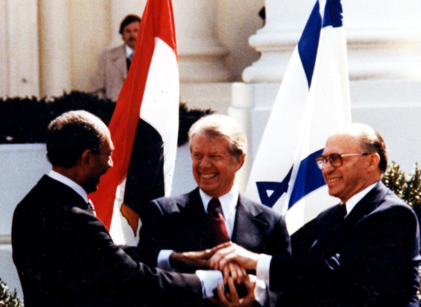 Menachem Begin and Anwar as-Sādāt signing the Israel-Egypt peace agreement, mediated by US President Jimmy Carter.